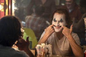 "Arthur Fleck (Joaquim Phoenix) ""puts on a happy face"" in the movie ""Joker."""